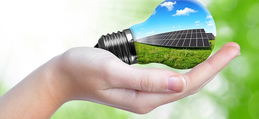 Schützende Hand umfasst Glühbirne mit Solar Modulen 2015